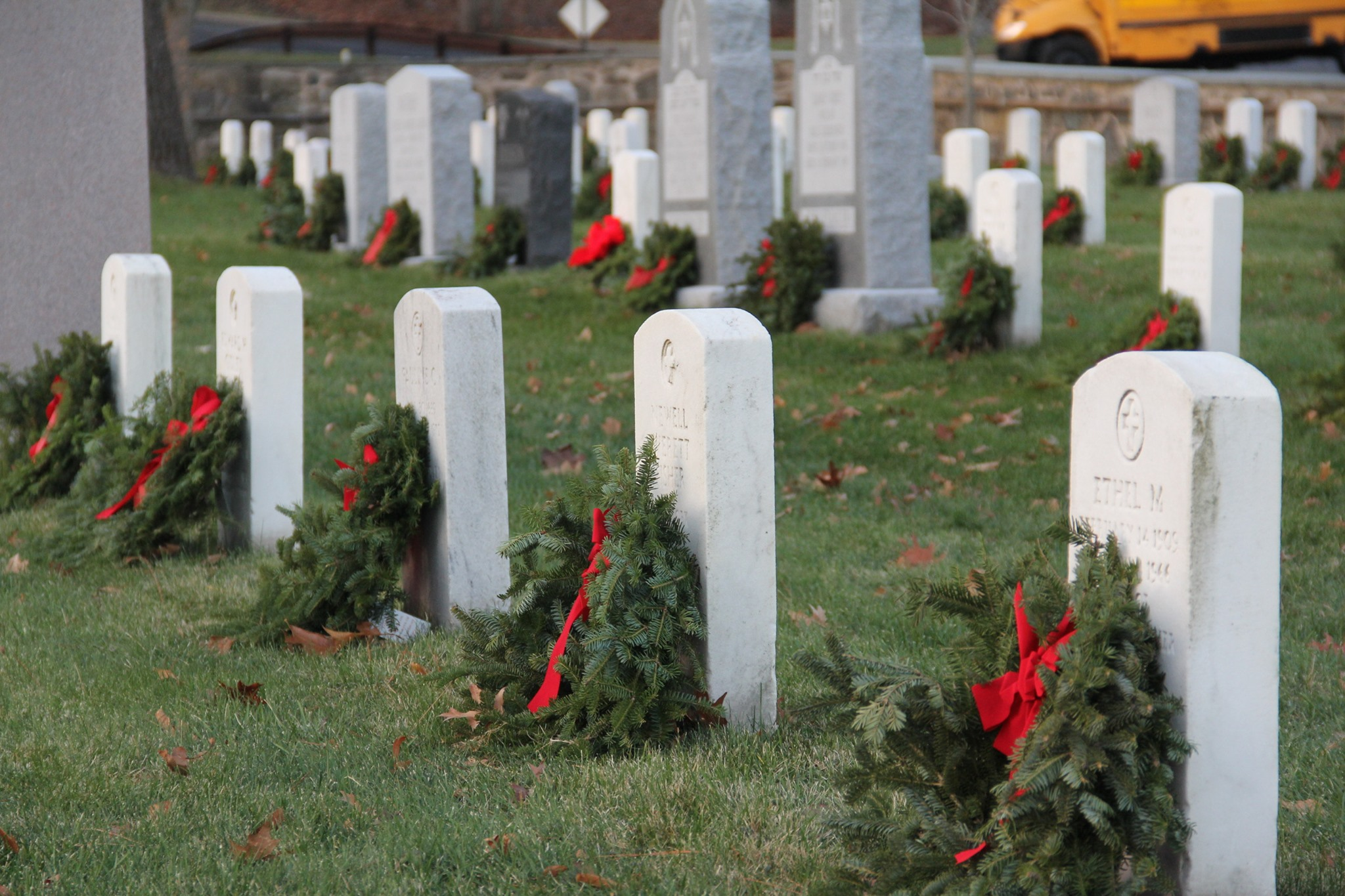 tombstones with wreaths placed on them