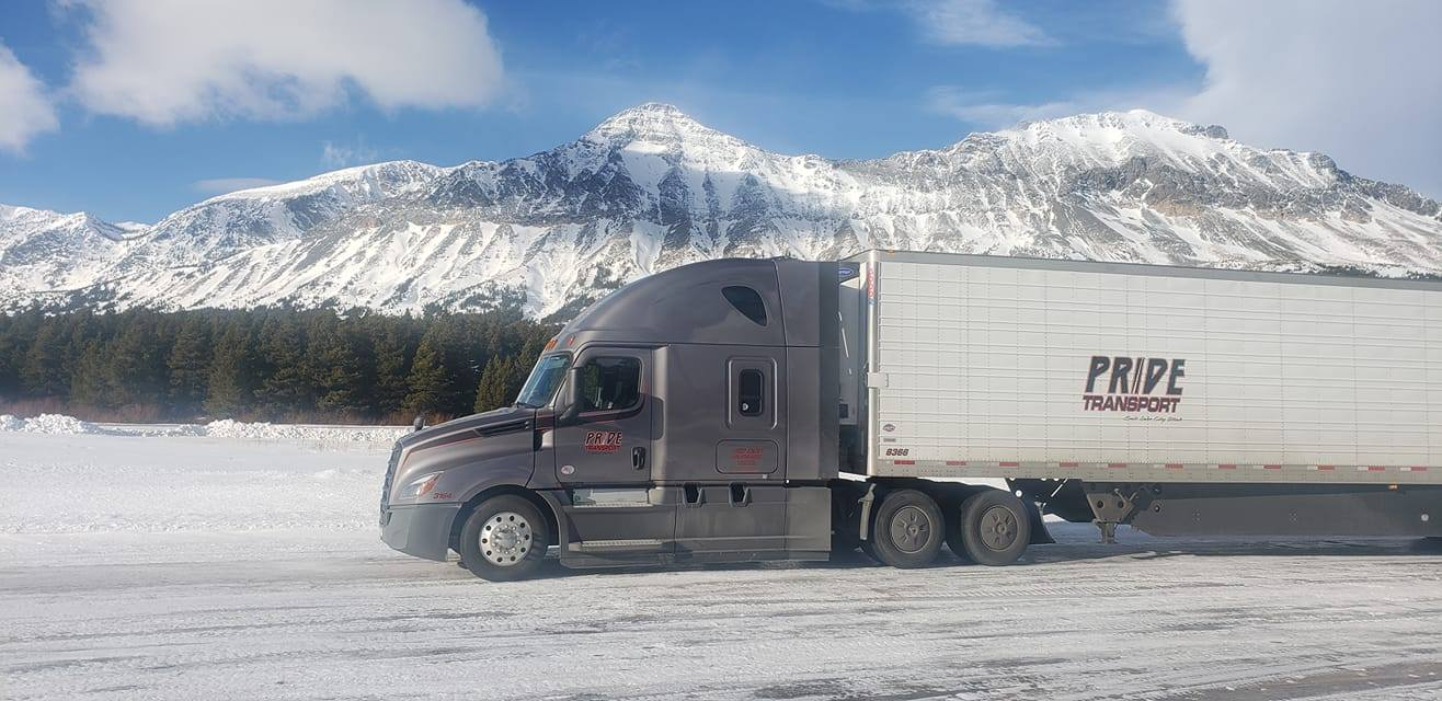 large diesel truck driving through the snow