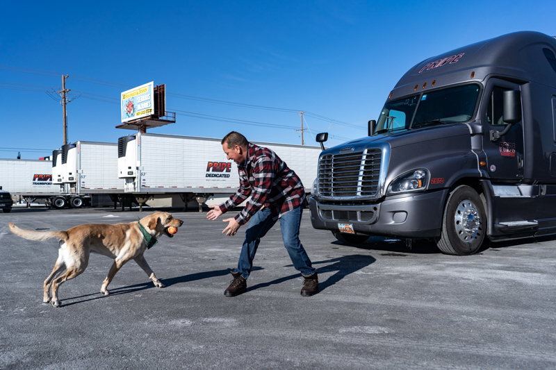 pride truck driver playing with dog