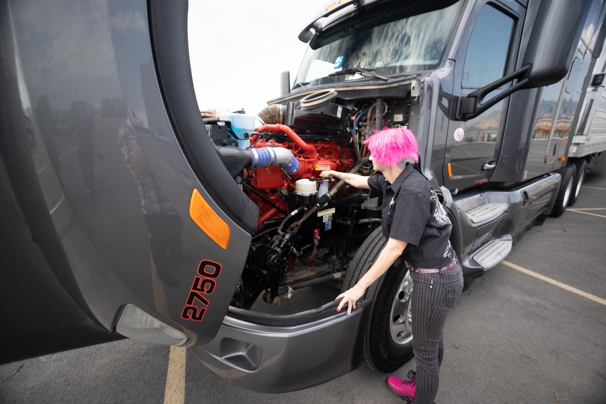 pride driver looking under hood of semi truck