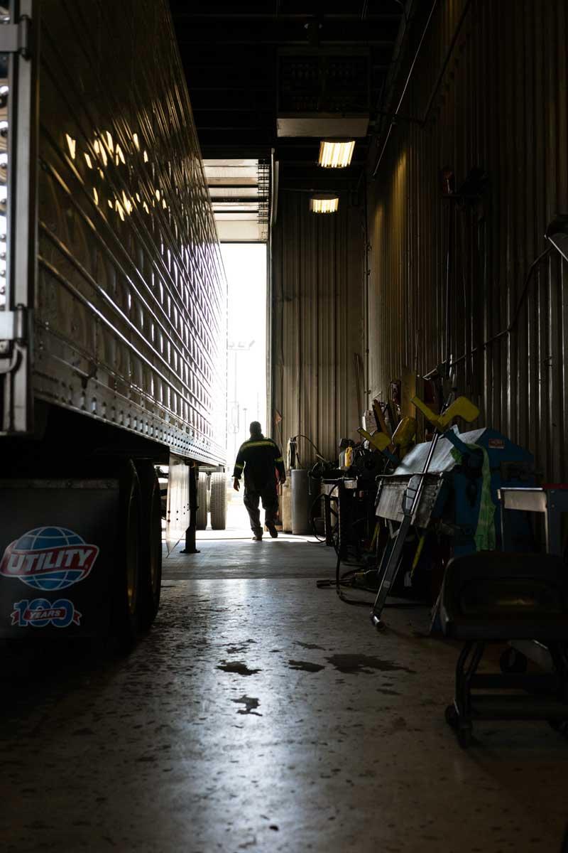 diesel tech walking next to a semi truck trailer in the shop