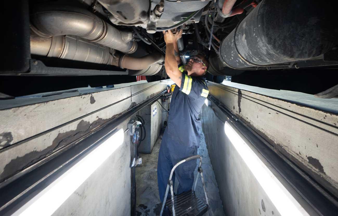 diesel technician working under a semi truck