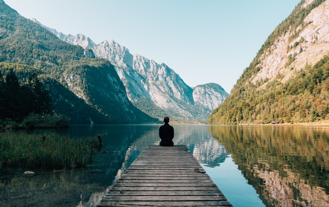 man sitting on dock looking at lake and mountains