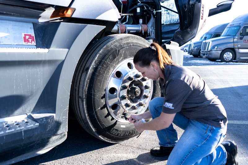 female truck driver inspecting tire